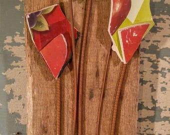 Broken pottery flowers in Reds and greens, with piano flower stems and old rusty Hardware embellishments