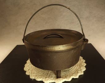 Cast iron three footed pot with cast iron lid