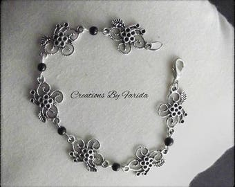Bracelet curb chain with connector in the shape of flower and black beads