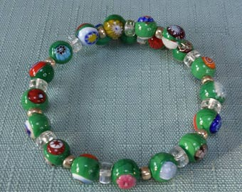 Green beaded bracelet with multi-colored designs.
