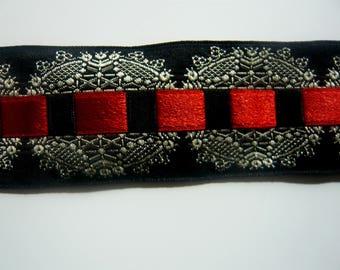 Galon en satin noir de coton,  fausse broderie, entrelacé d'un ruban rouge