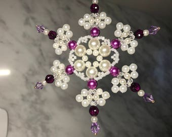 Snowflake for a Christmas tree of twinkling white pearls and purple beads. Home decor. A gift to friends and relatives. Handmade.