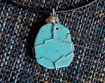 Wire wrapped turquoise pendant on leather necklace.
