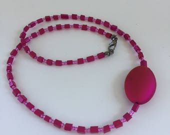 Striking and elegant hot pink bead necklace with large oval feature bead.