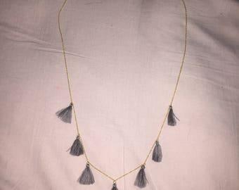 Long grey tassel necklace.