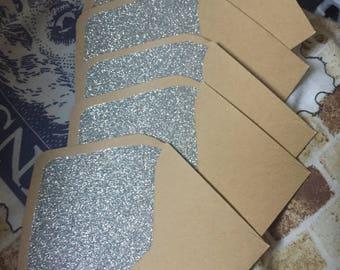 Five silver glitter and kraft envelopes