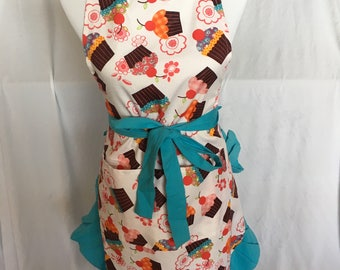 Women's apron with pockets. Cupcake print with blue straps and pleats.