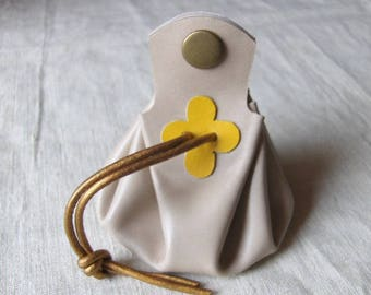 Coin purse is off-white leather with yellow clover