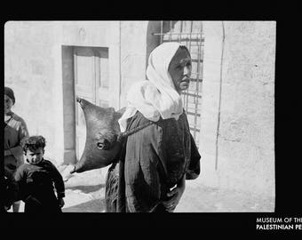 Bethlehem woman carrying water in a goatskin