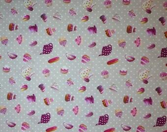 Coupon de tissu avec des gourmandises roses sur fond gris à pois blanc