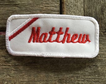 """Matthew. A white work shirt name patch that says """"Matthew"""" in red print with white border"""