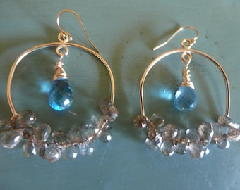 Topaz Arch Earrings are golden arches completed by curves of sparkling Topaz briolettes with glorious blue Topaz briolettes dangling above.