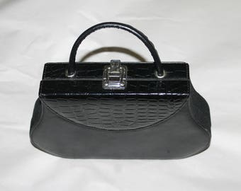 This  is kind of a box purse, it is not leather, it has a buckle closure, it has one handle, Nice design, Mirror inside, very good condition