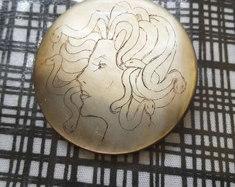 Hand carved face of Medusa (gorgon) mother of pearl button.