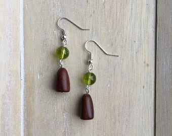 Silver dangle earrings with peridot beads and long wooden beads.