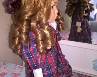 Porcelain doll in Edwardian girl's costume of tartan and red velvet. She has strawberry blonde hair. A collectible Leonardo doll. With stand