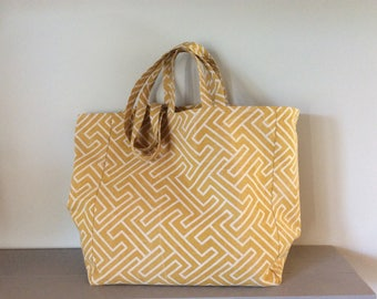 Tote bag yellow with white graphic lines.
