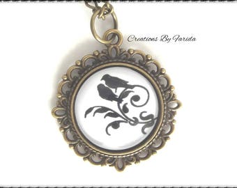Pretty necklace with cabochon on the grounds of birds on a branch on bronze color support