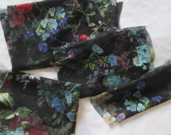 Four pieces of black fabric printed with flowers