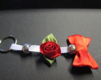 Key ring in bead mounted on a white satin ribbon