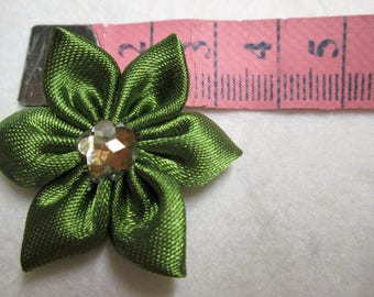 Green satin with a flower is adorned with a gold tassel