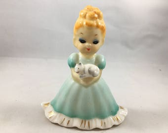 Vintage Little Blonde Girl in a Blue Dress Holding a Cat Figurine