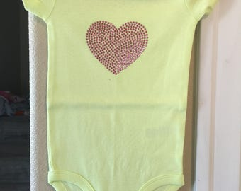 Yellow onesie with a pink heart