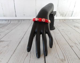Distictive silver open cuff bracelet with blood red beds and square white with red flower beads.