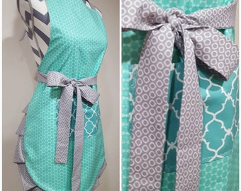 Adult apron. Woman's apron. Teal circles on main. Darker teal pattern on pocket. Gray circle pattern on ties and frills.