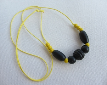 boho necklace with large wooden beads and bright yellow and black waxed cotton cord
