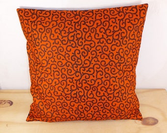 Cushion cover 40 x 40 tone orange African Wax fabric and small black patterns.