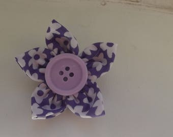 Purple fabric flower brooch.