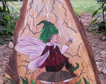 sweet little Elf is painted on a piece of wood...
