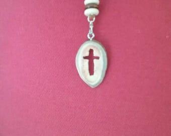 Cross carved into deer antler pendant