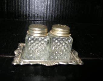 Individual salt and pepper shakers with silver plated tray