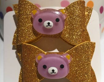 Beautiful foam bow with custom appliqué (glittery gold with lilac bear) on an alligator clip. (Set of 2).