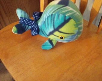 Whale in fleece multicolor, blue, yellow, and green. Hypoallergenic stuffing. Safety lock eyes. Measures 9 inches long.