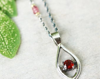 Silver leaf shape necklace and garnet at the center with multi pink sapphire beads secondary on oxidized sterling silver chain