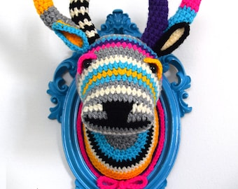 Crochet deer head in a blue frame.