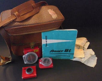 Antique Bauer leather camera case with shoulder strap. Includes book and Accessories as noted.