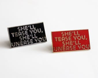 "She'll Tease You, She'll Unease You Red Gold Black Silver Typography pin // 1.25"" hard enamel lapel pin, feminist song lyrics, 1980s"