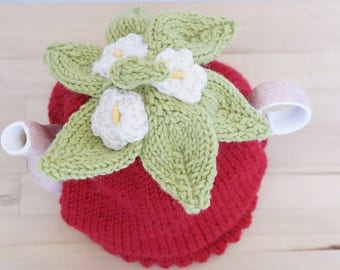 Red tea cosy with yellow and white flowers, light green leaves, tea cozy
