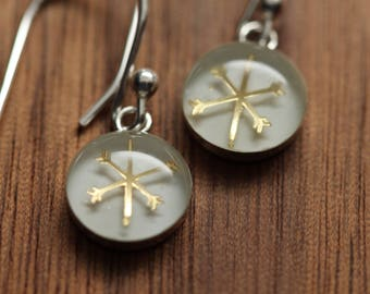 Tiny Golden snowflake earrings made from recycled Starbucks gift cards. sterling silver and resin.