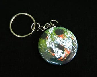 Keychain with a head of panda on green background