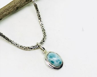 10% Larimar pendant set in sterling silver (92.5). Length -.90 inch. Stone - 14x10mm. Genuine natural larimar stone.