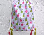 Pineapple-print crossbody bag with drawstring. Fun tropical fruit purse in white, pink, and green. Show off your summer style!