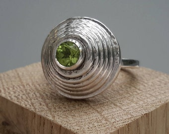 Concentric hammered silver ring set with 5mm round brilliant peridot