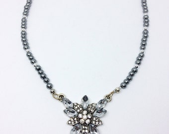 Gray beaded necklace with flower pendant