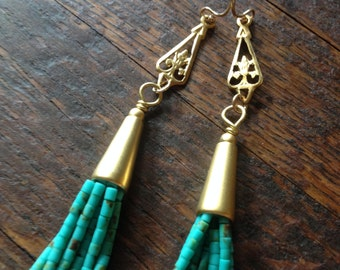 Turquoise beaded tassel earrings on petite golden drops.