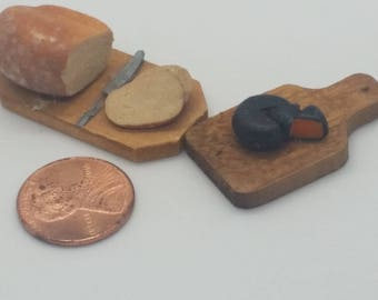 Handmade miniature wooden loaf of bread on cutting board and cheese on a cutting board